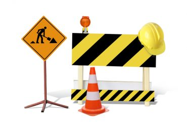 Road construction sign, yellow and black striped barrier with warning light and yellow helmet, marker post isolated on white